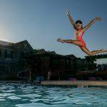 Fille sautant dans le grand bain, élève de cours particulier de nage en eau profonde